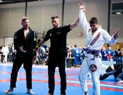 Kial Wilkins has his arm raised in victory over a black belt.